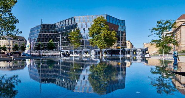 Bibliothek der Albert-Ludwigs-Universität mit Straßenbahn und Wasserbrunnen